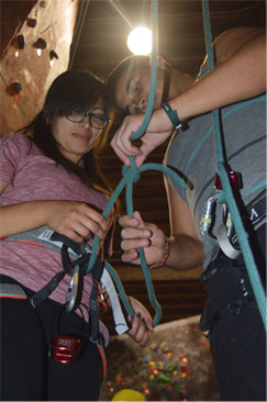 "A LEAP volunteer shows a student ""the ropes"" of climbing on the rock wall."