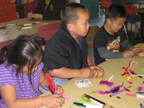 Children use their imagination to create a potato buddy.