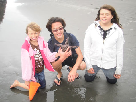Volunteer and children discover starfish at beach.